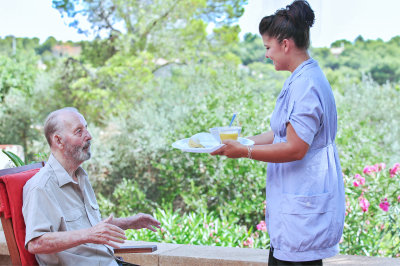 young woman giving meal to a senior man