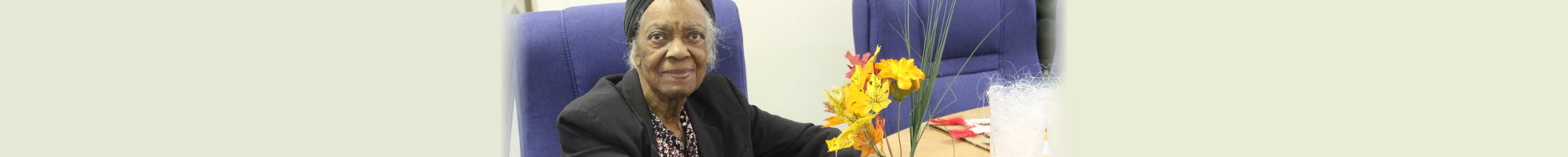 Elderly Woman smiling with flowers on the table