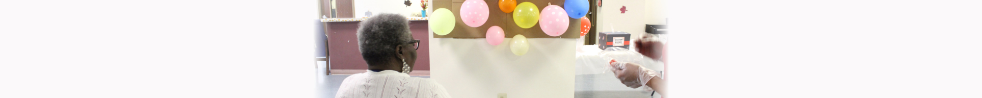 Old Man sitting with the balloons in his front